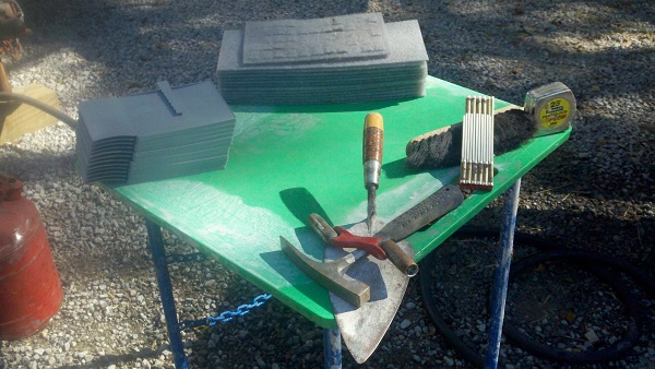 Shown are a mud board and more tools of the masonry trade.