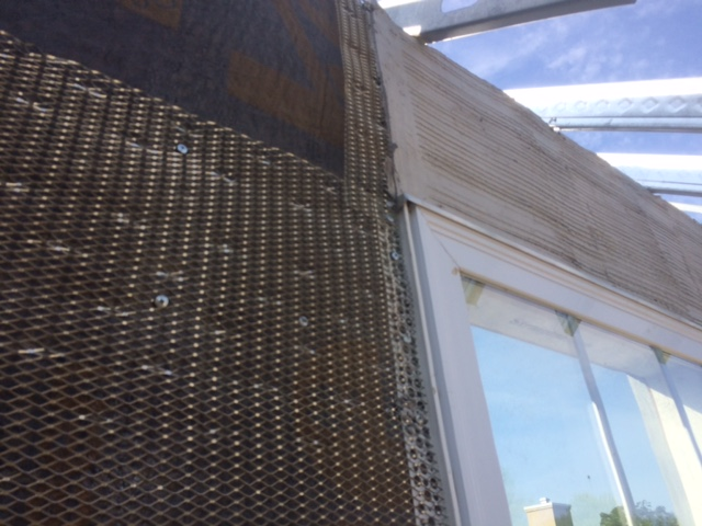 Shown is a close-up view of Driwall Rainscreen, casing bead along a window, and metal lath installed with part of the scratch coat applied on top of the window.