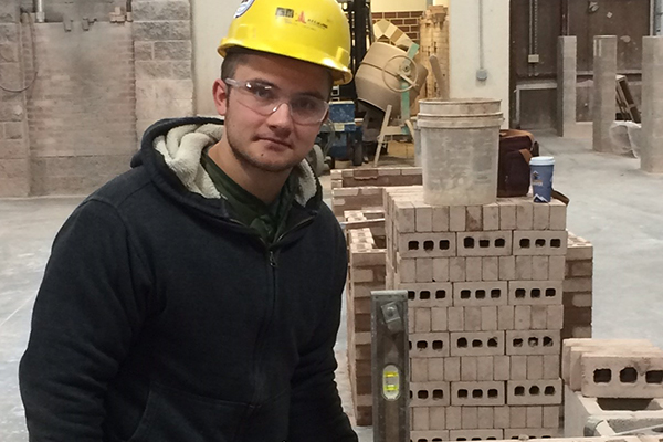 Johnathon Crouch, a masonry apprentice with a Connecticut bricklayers' union, builds a wall as part of his training.